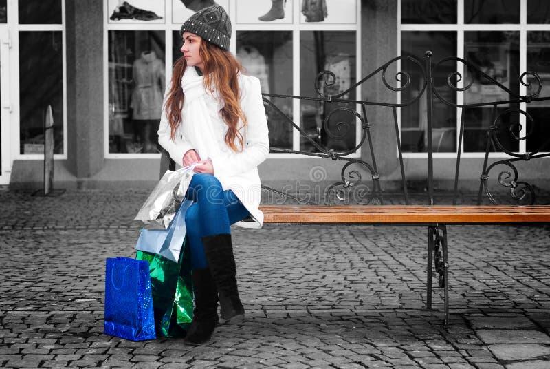 Jonge vrouwenzitting op een bank stock foto