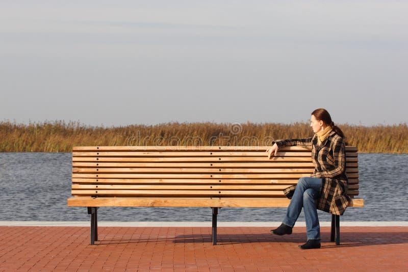 Jonge vrouwenzitting op een bank stock afbeeldingen
