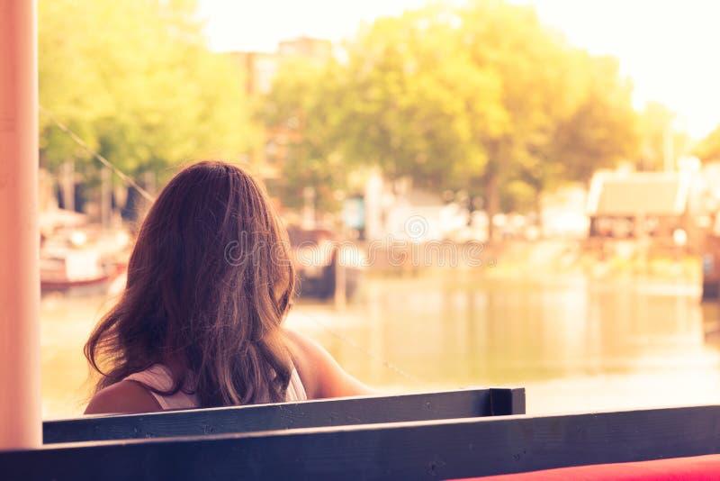 Jonge vrouwenzitting op een bank die op het dok van de baai letten bij s stock afbeeldingen