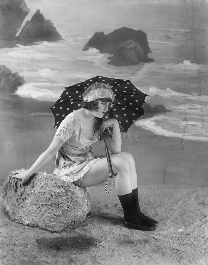 Jonge vrouwenzitting op een bolder op het strand, holding een paraplu (Alle afgeschilderde personen leven niet langer en geen lan royalty-vrije stock fotografie