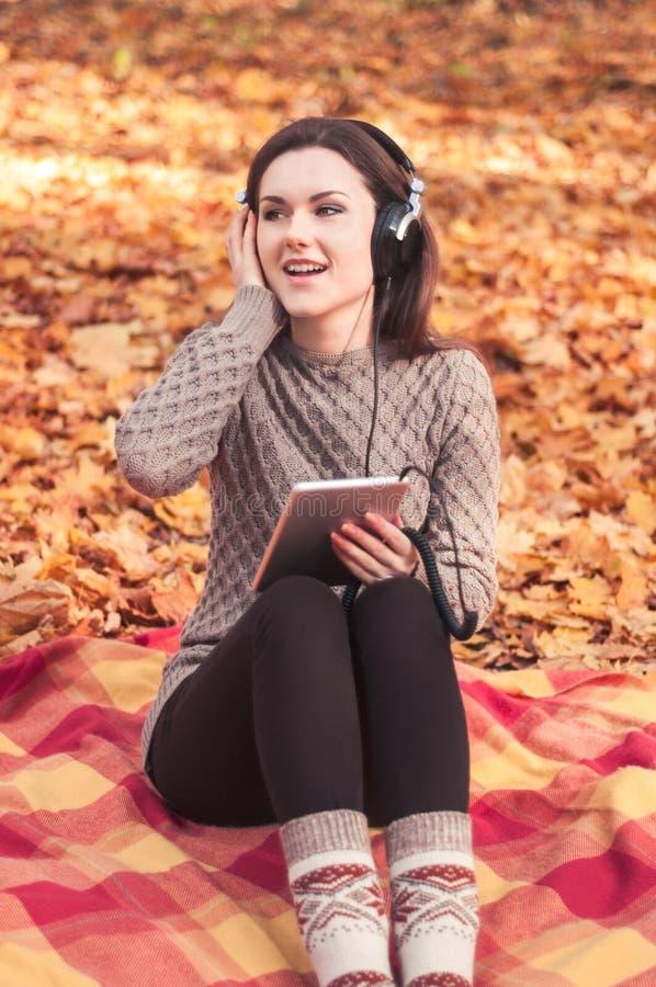 Jonge vrouwenzitting op een deken en het luisteren aan de muziek stock foto's