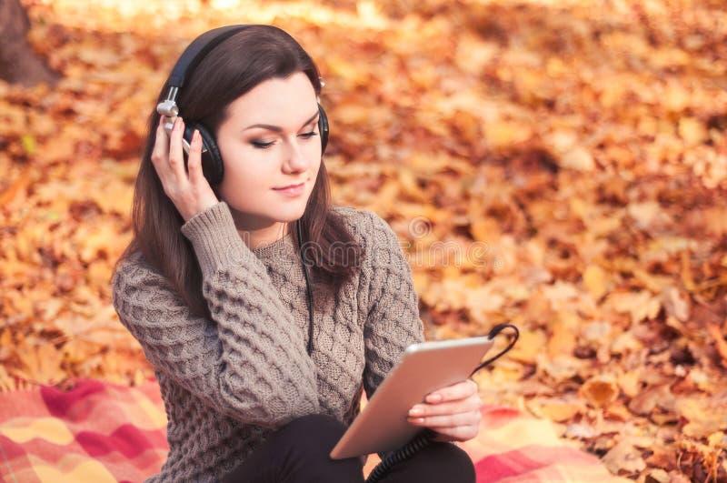 Jonge vrouwenzitting op een deken en het luisteren aan de muziek royalty-vrije stock foto's
