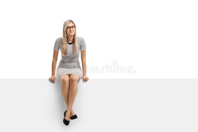 Jonge vrouwenzitting op een paneel en het bekijken de camera stock afbeelding