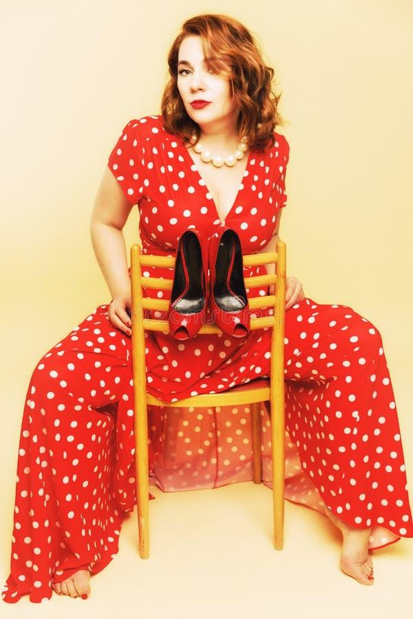 Jonge vrouwenzitting op een stoel in een lange heldere kleding, op een stoel hangende schoenen royalty-vrije stock foto