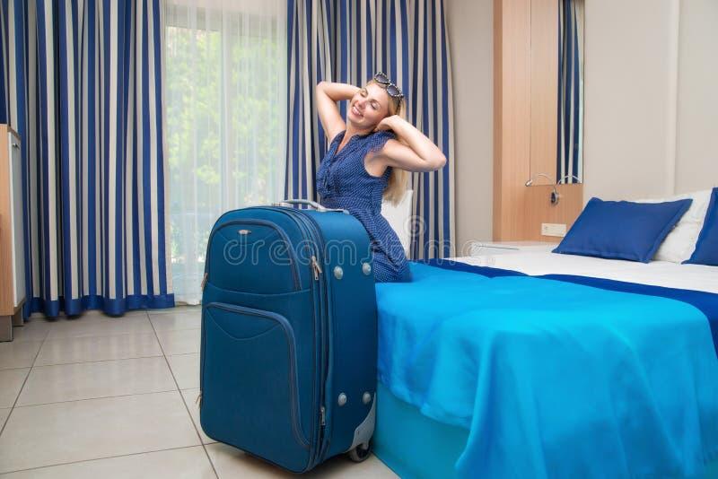 Jonge vrouwenzitting op het bed in de hotelruimte Rust na een lange reis stock afbeeldingen