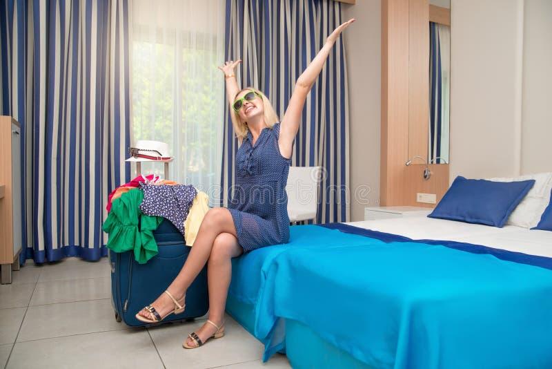 Jonge vrouwenzitting op het bed in de hotelruimte Rust na een lange reis royalty-vrije stock afbeeldingen