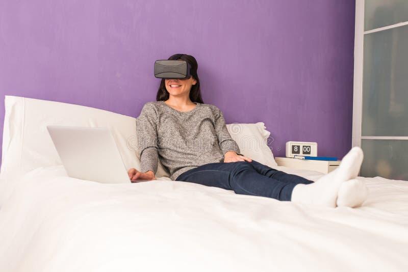Jonge vrouwenzitting op het bed die thuis en virtua ontspannen gebruiken royalty-vrije stock foto