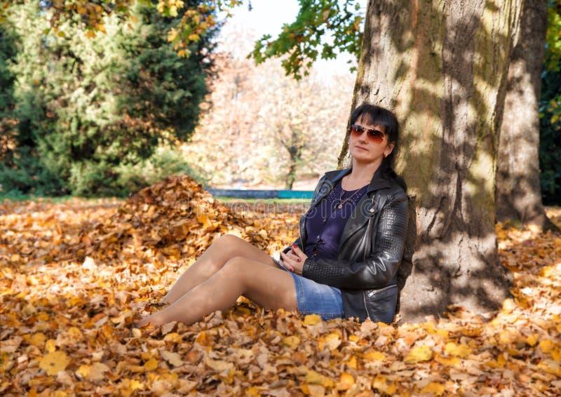 Jonge vrouwenzitting op het gras in het park in de herfst royalty-vrije stock foto