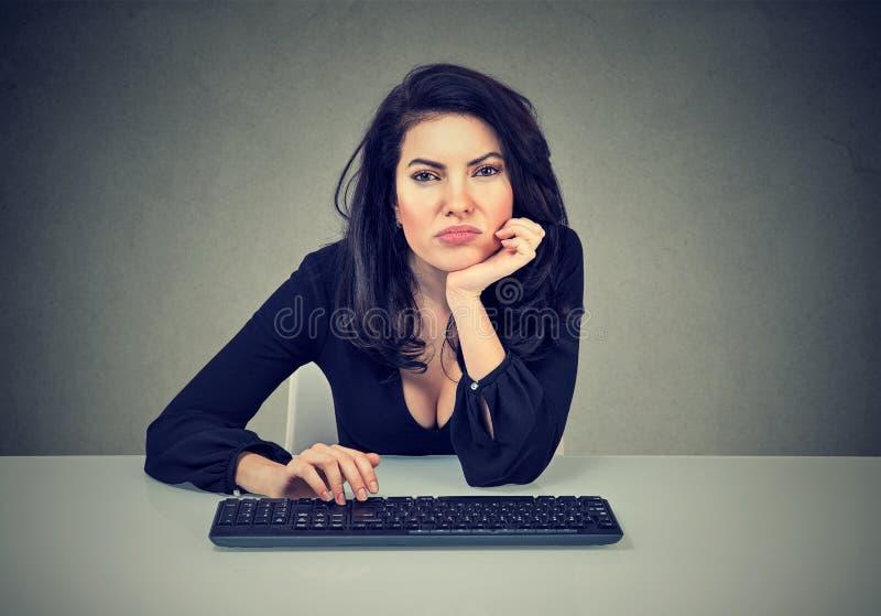 Jonge vrouwenzitting op het werk en het uitstellen zijnd lui en afgeleid stock foto