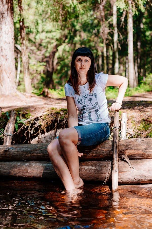 Jonge vrouwenzitting op logboeken en verminderd haar voeten in de rivier royalty-vrije stock foto's