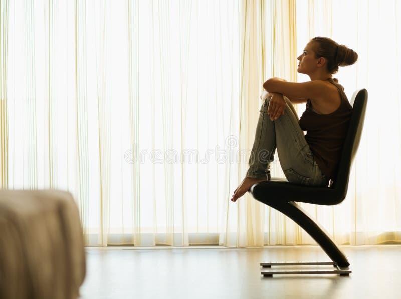 Jonge vrouwenzitting op moderne stoel dichtbij venster stock fotografie