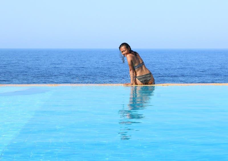 Jonge vrouwenzitting op rand van pool door overzees stock foto