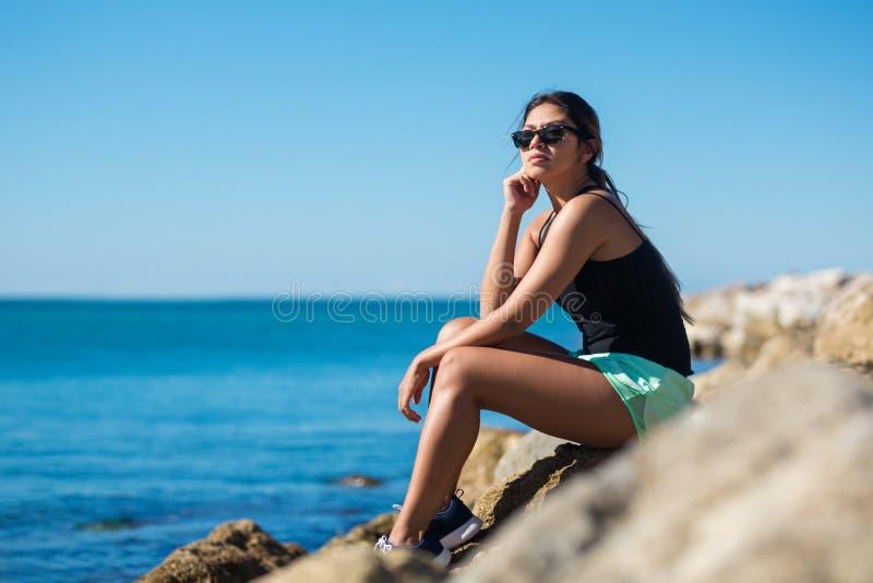 Jonge vrouwenzitting op rots bij kust het denken royalty-vrije stock foto
