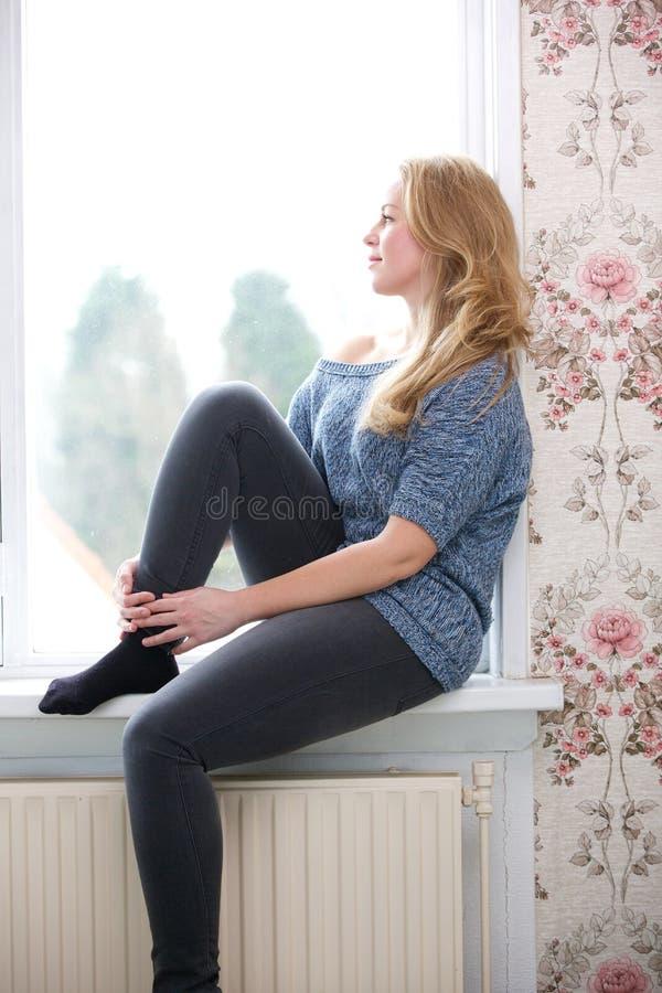 Jonge vrouwenzitting op vensterbank thuis stock foto