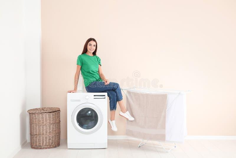 Jonge vrouwenzitting op wasmachine thuis stock foto