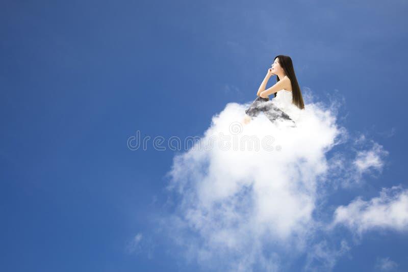 Jonge vrouwenzitting op wolk en het denken stock foto's