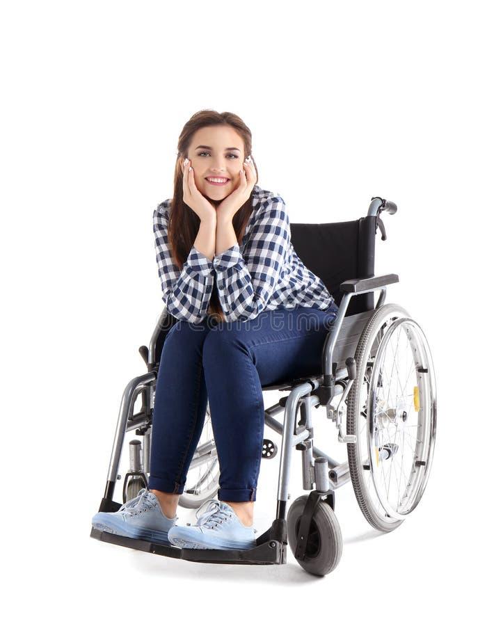 Jonge vrouwenzitting in rolstoel op witte achtergrond stock foto's