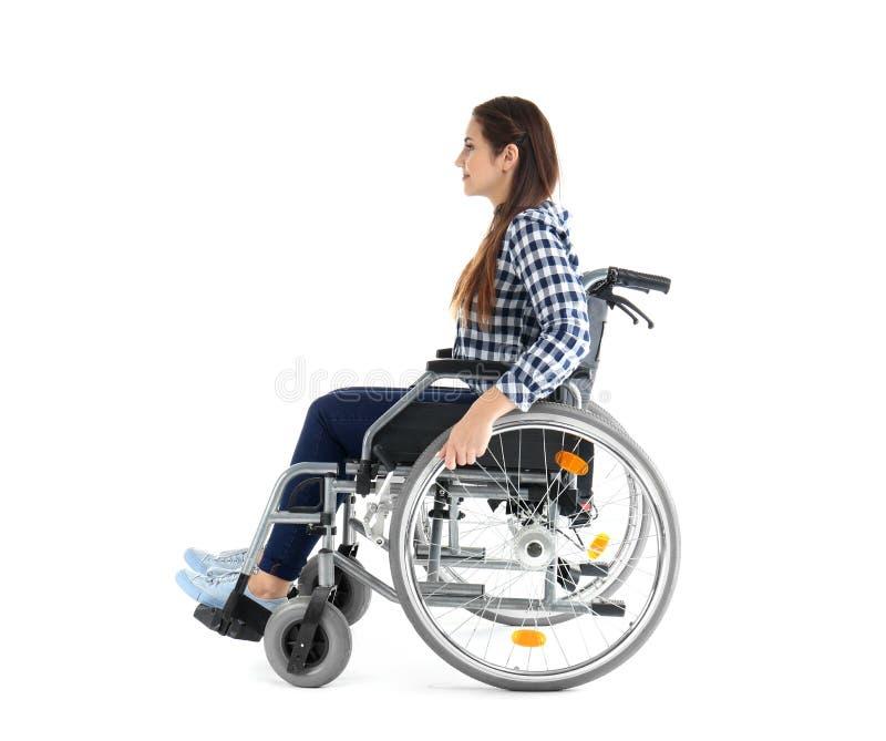 Jonge vrouwenzitting in rolstoel op witte achtergrond stock afbeeldingen