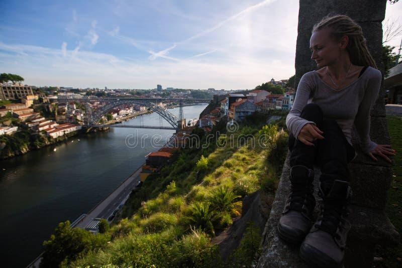 Jonge vrouwenzitting tegen de achtergrond van Dom Luis I brug, Porto royalty-vrije stock afbeelding