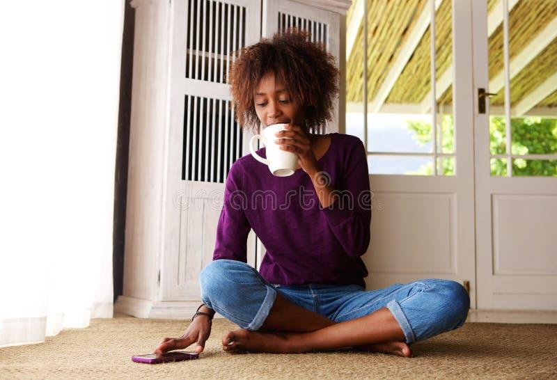 Jonge vrouwenzitting thuis met koffie en mobiele telefoon royalty-vrije stock afbeelding