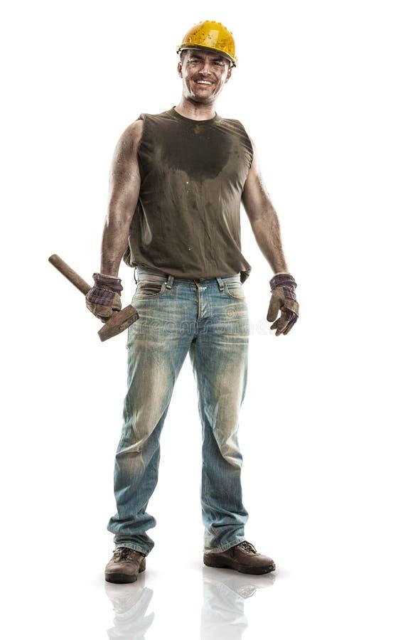 Jonge vuile Arbeidersmens die met Bouwvakkerhelm een hamer houden stock afbeelding