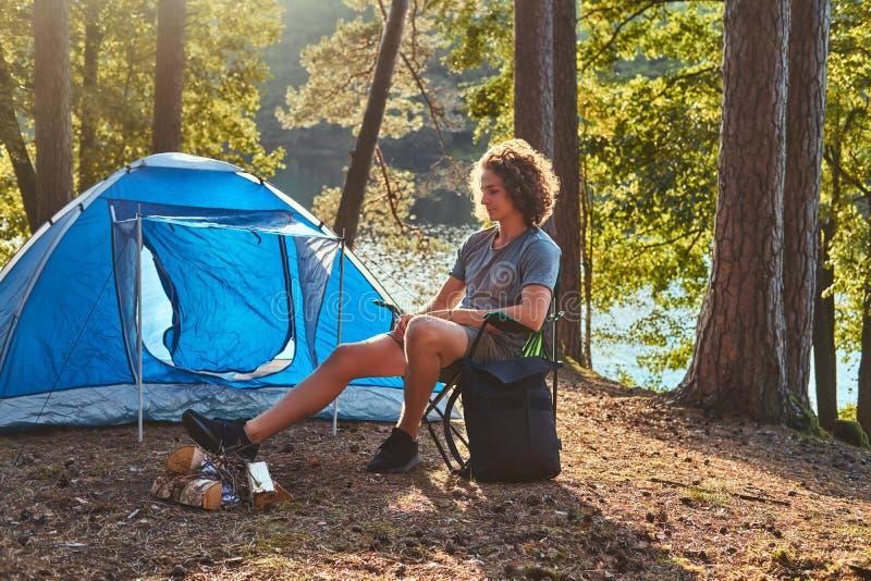 Jonge wandelaarkerel met krullende haarzitting op een stoel bij kamp in het bos stock afbeeldingen