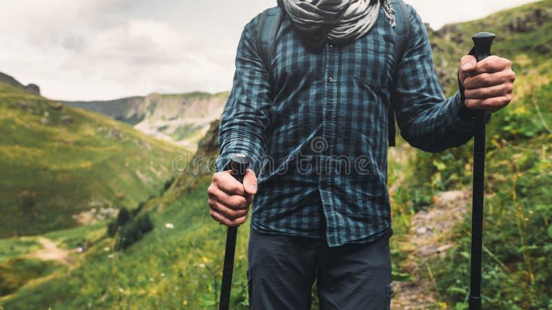 Jonge Wandelaarmens die met Rugzakken en Stokken op een Berg lopen Het Openluchtconcept van het reisavontuur royalty-vrije stock foto