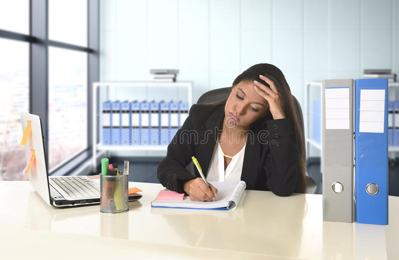 Jonge wanhopige bedrijfsvrouw die aan spanning lijden die bij het bureau van de bureaucomputer werken stock fotografie