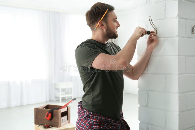 Jonge werkende mens het bevestigen klerenhaak op muur thuis royalty-vrije stock afbeeldingen
