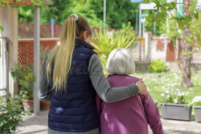 Jonge werker uit de hulpverlening die met het bejaarde in de tuin lopen stock foto