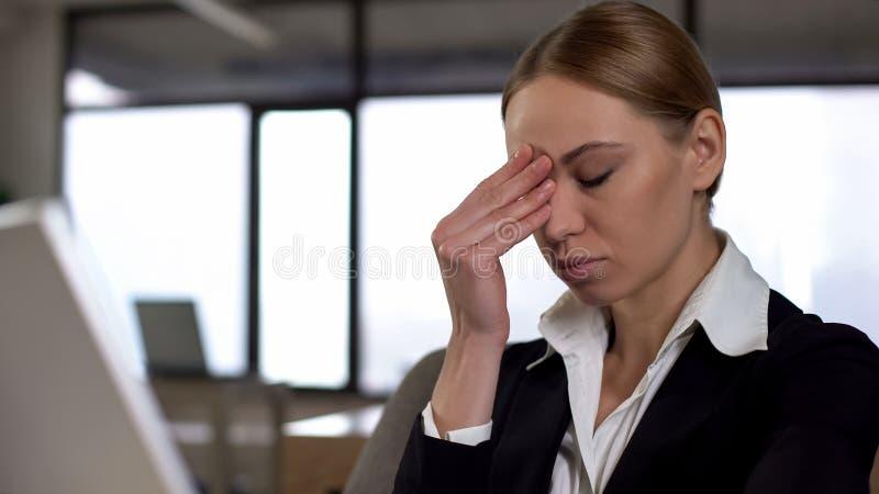 Jonge werknemer die aan hoofdpijn die lijden, van complex project wordt vermoeid, overwerkenconcept stock fotografie
