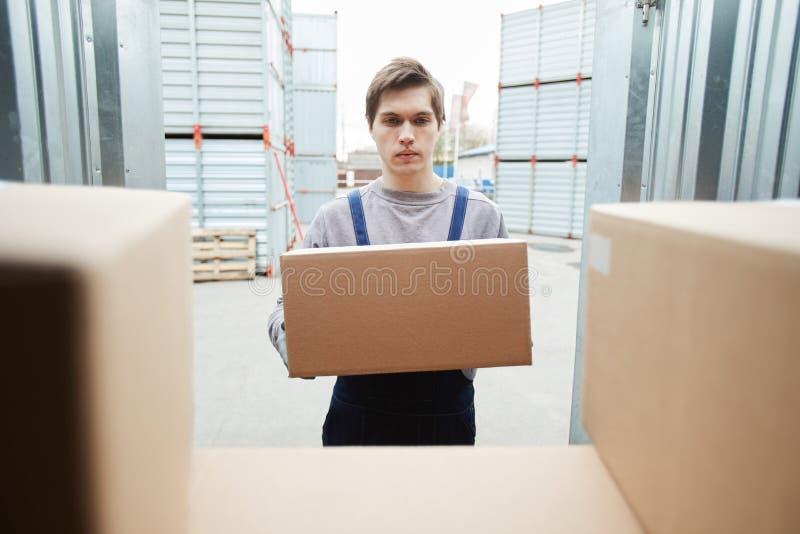 Jonge werknemer die doos in container zetten stock fotografie