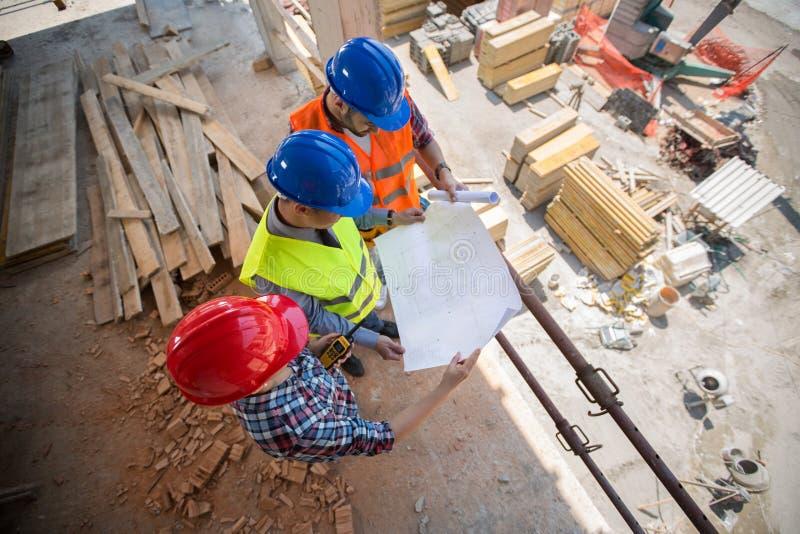 Jonge werknemers die blauwdruk controleren bij de bouw van plaats royalty-vrije stock foto