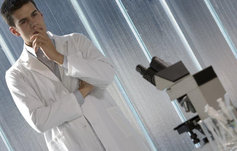 Jonge wetenschapper die in zijn laboratorium denkt stock afbeelding
