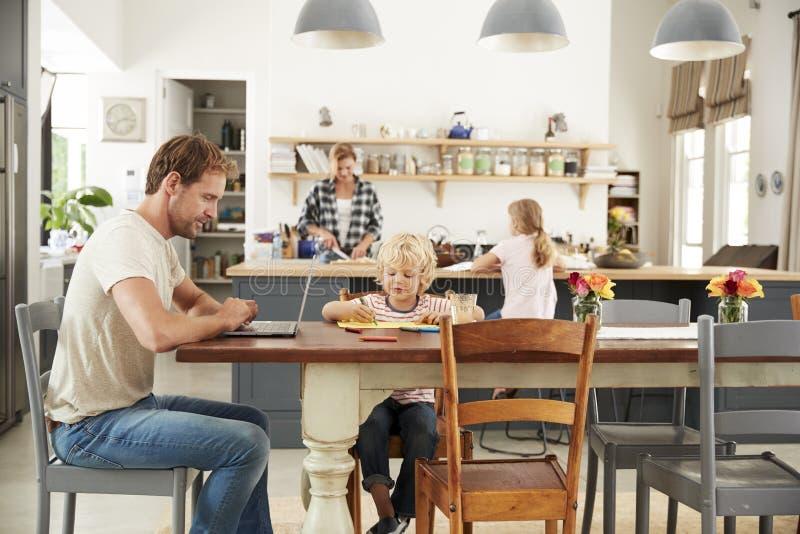 Jonge witte familie bezig het werken in hun keuken stock fotografie