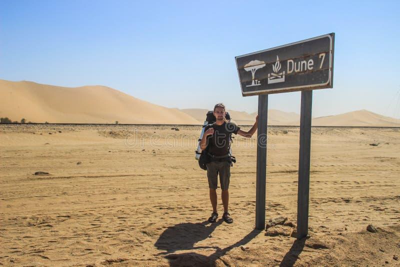 Jonge witte Kaukasische mannelijke reiziger met een rugzak die zich naast Duin 7 teken in het Nationale Park van Sosusfle bevinde royalty-vrije stock afbeelding