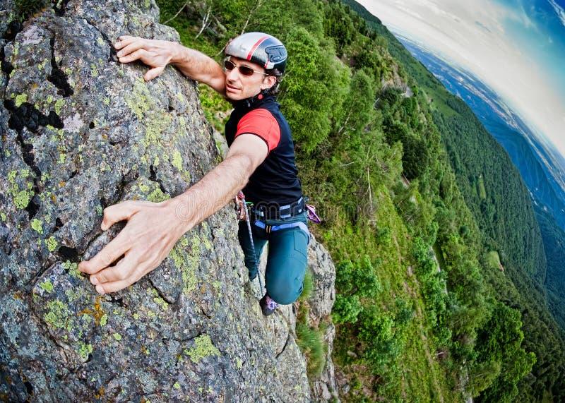 Jonge witte mens die een steile muur beklimt stock foto's