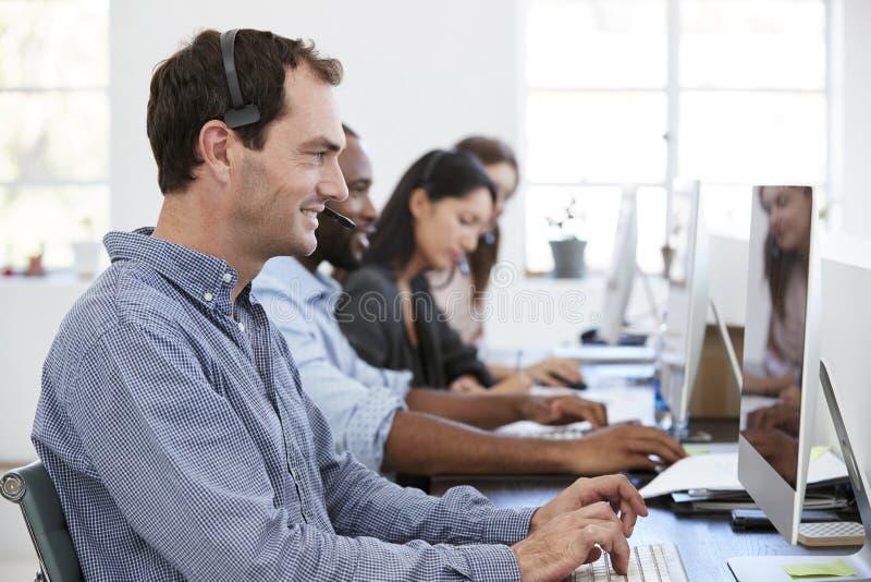 Jonge witte mens met hoofdtelefoon die bij computer in bureau werken stock fotografie