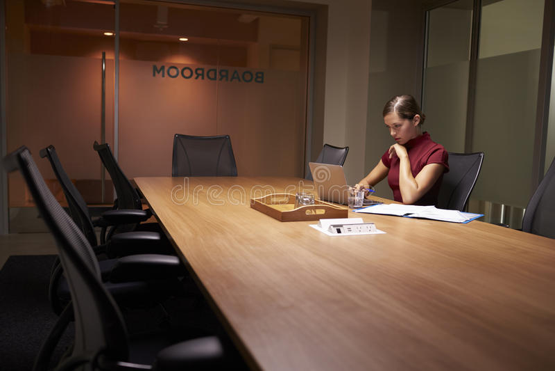 Jonge witte onderneemster die alleen laat in een bureau werken stock afbeeldingen