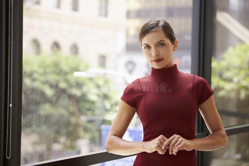 Jonge witte onderneemster die door een venster op het werk leunen royalty-vrije stock fotografie
