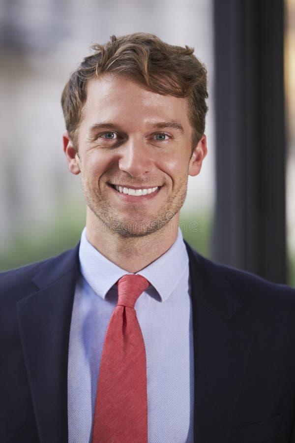 Jonge witte zakenman die, verticaal portret glimlachen stock foto