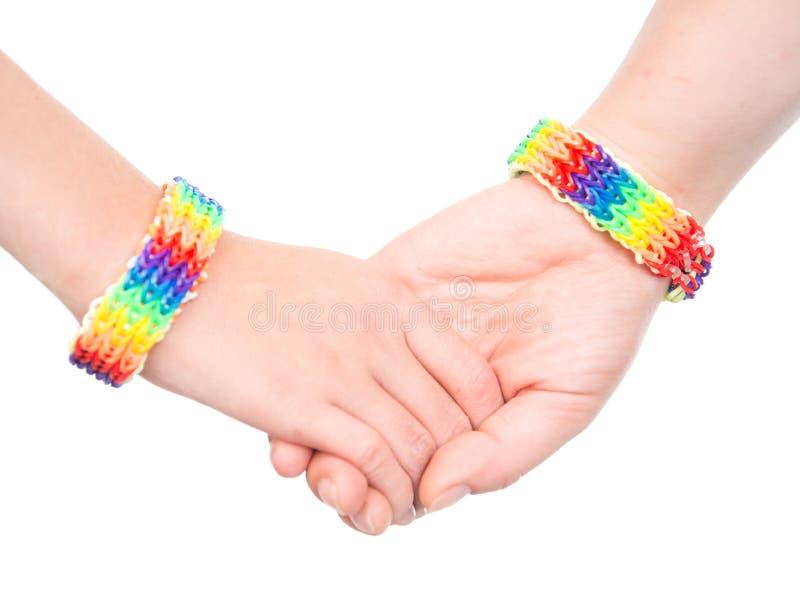 Jonge woman& x27; s handen met een armband als regenboogvlag die wordt gevormd Geïsoleerd op wit royalty-vrije stock afbeeldingen