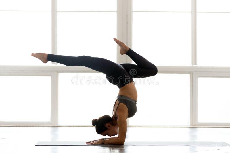 Jonge yogi aantrekkelijke vrouw het praktizeren yoga, die handstand pos doen stock afbeeldingen
