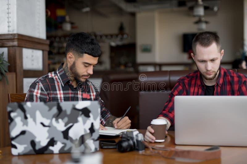 Jonge zakenlieden die online het werken blogging door laptop computers in koffie royalty-vrije stock afbeeldingen