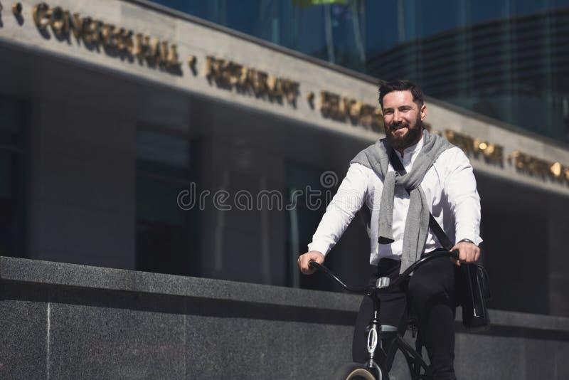 Jonge zakenman berijdende fiets op stedelijke straat stock afbeeldingen