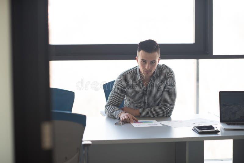 Jonge zakenman bij zijn bureau in bureau stock fotografie