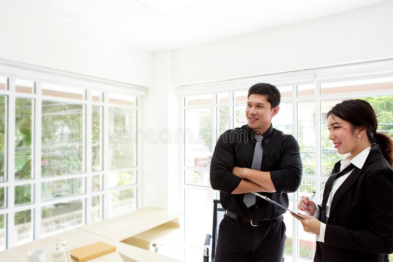 Jonge zakenman in bureau Twee bedrijfsberoeps die samenwerken Man en vrouwen het aantrekkelijke kijken royalty-vrije stock foto