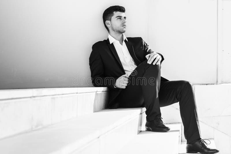 Jonge zakenman dichtbij een bureaugebouw die zwart kostuum dragen royalty-vrije stock foto