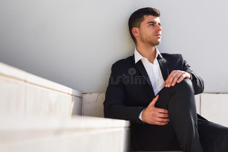 Jonge zakenman dichtbij een bureaugebouw die zwart kostuum dragen stock afbeeldingen