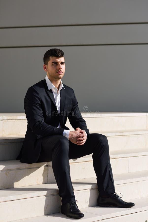 Jonge zakenman dichtbij een bureaugebouw die zwart kostuum dragen stock fotografie